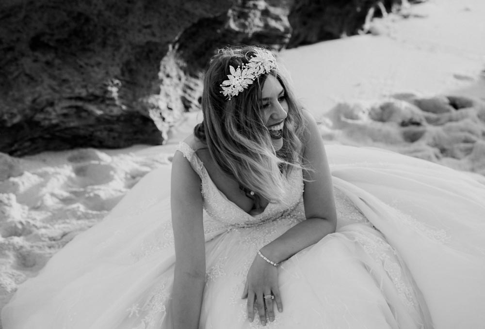 black and white image of a smiling bride on beach